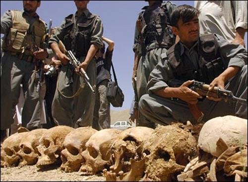 Afghan officials pose near a row of skulls. Pics by Massoud Hossaini